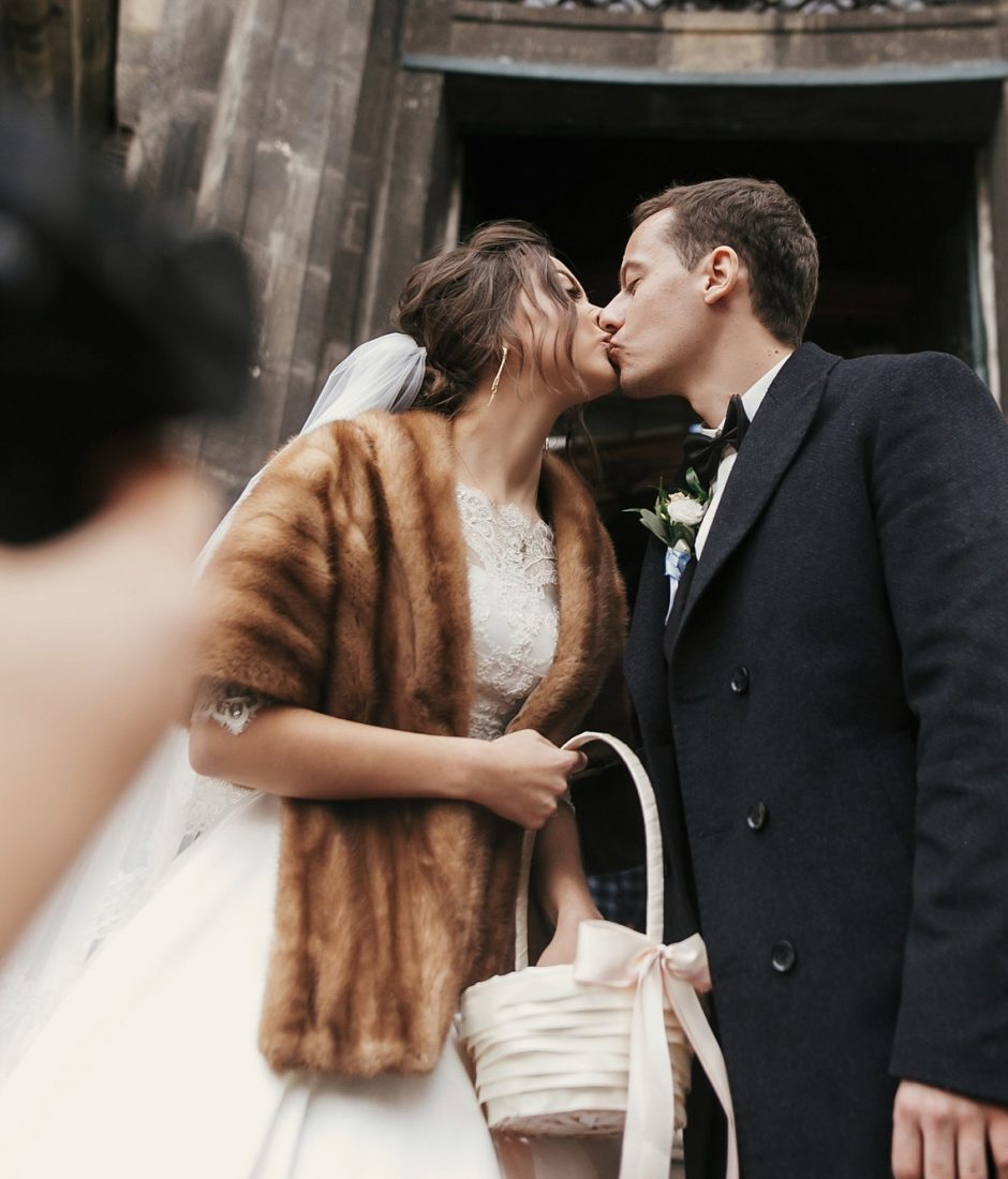 photographer taking photo of gorgeous bride in coat and stylish groom near church